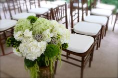 Rustic wedding decor with green and white flowers including, hydrangea, roses, garden roses, dahlias, succulents, hanging amarathus and moss.