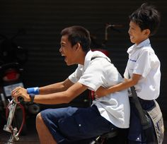 These boys are truly having an ecstatic moment as they speed race down the road after school - Siem Reap, Cambodia.
