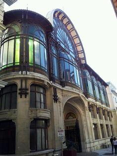 La Source Cachat. Evian-les-Bains. France. Au milieu de la rue Nationale, rue la plus commercante d'Evian-les-Bains, ce bâtiment de style Art Nouveau abrite aujourd'hui le hall d'information des eaux minérales Evian. Il date de 1903, et est l'oeuvre de l'architecte Jean Hébrard. Les décors sont de Raoul Ubac et d'André Beaudin. L'édifice a été construit pour la Société des eaux minérales d'Evian.