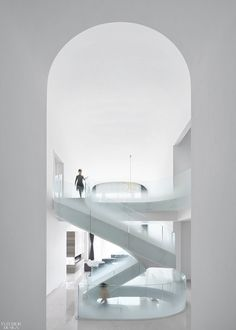 """An elliptical staircase—a grand """"sculptural gesture,"""" Zerebecky notes—connects the three floors. The basement level features a piano area, tearoom, study, mah-jong room, gym, and home theater. The airy central space one flight up is flanked by two kitchens, three guest and staff bedrooms, and the living/dining area. The floor above, from which a balcony overlooks the living space below, contains the master suite and a pair of children's bedrooms."""