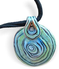 This pendant by Patricia Roberts-Thompson is the result of her playing with Samantha Burroughs' Oyster Watercolor tutorial. Its loose circles and watery colors make your eyes dive right in. Patricia added distressing powders to her color combin [...]