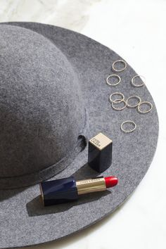Fall look: chic hat, gold rings, and Pure Color Envy Lipstick in Carnal (the BEST red lipstick shade) (Beauty Products Flatlay) Red Lipstick Shades, Best Red Lipstick, Red Lipsticks, Flat Lay Photography, Makeup Photography, Jewelry Photography, Product Photography, Flatlay Makeup, Ringe Gold