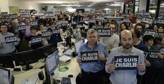 """Journalists hold placard reading """"I am Charlie"""" as they hold a minute of silence Wednesday at the Paris newsroom of French news agency Agence France Presse, following the attack by gunmen in the offices of the French satirical weekly Charlie Hebdo."""