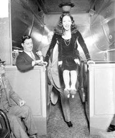 Lupe Velez bracing her hands on two low counters and holding her feet in the air in a passenger train car near Chicago, Illinois, 1929. Two men are standing behind her, and an unidentified man is partially visible sitting in the foreground.