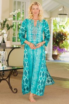 """Elaborate hand-sewn embellishment - silver seed beads, turquoise faceted """"jewels,"""" unique pompom beads and white roping - light up the neckline of this exotic caftan, fashioned in a stunning ikat print with contrasting designs in vibrant turquoise. Cool and lightweight with high side slits, it's ready for lounging or entertaining. Due to their artisanal origin, no two are alike. Cotton. Misses 54"""" long. Nyoman Caftan #29266"""