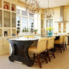 Large kitchens require hefty light fixtures. The interlocking circles of the chandeliers are echoed in the detail on the chairs, and in the metal accents and rounded feet of the island.