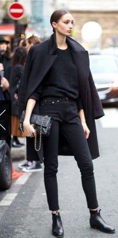 Black duster coat, jumper, skinny jeans, Chanel bag, flat ankle boots, hair Bun