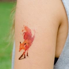 A small but fiery looking fox tattoo. Using colored ink the small fox is embedded into the arm making it look like it's on fire and ready for battle.