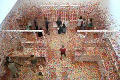 """Children and adults cover an all-white room with colorful stickers in Yayoi Kusama's latest """"Obliteration Room."""""""
