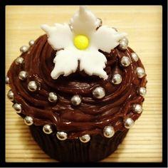 Cupcake Espiral em Flor Chocolate | Cupcake coberto com chocolate, confeitos e flor de pasta americana, massa do bolo e recheio de sua preferência.