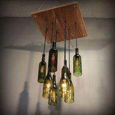 Kronleuchter aus Weinflaschen befestigt an Holzplatte