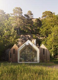 Trois petites cabines en bois et verre sur la côte norvégienne forment une…