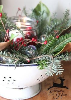 A Farmhouse Christmas-from The Everyday Home: Vintage Colander filled with greenery and a Mason Jar with fresh cranberries and a floating candle.