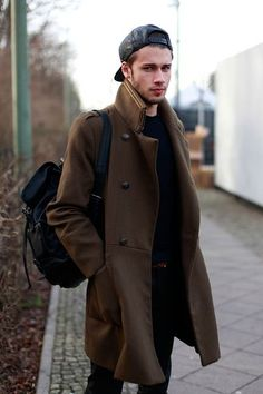 Consider wearing a brown overcoat and black jeans to look classy but not particularly formal.  Shop this look for $169:  http://lookastic.com/men/looks/baseball-cap-crew-neck-sweater-overcoat-backpack-jeans/7629  — Black Leather Baseball Cap  — Navy Crew-neck Sweater  — Brown Overcoat  — Black Canvas Backpack  — Black Jeans