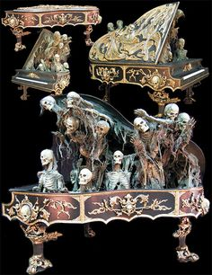 Beautifully detailed gothic piano features Grim Reaper relief sculpture on lid with skull and gold leaf details throughout body, when activated a mob of 13 skeletons come screaming out from under the lid…