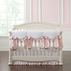 White and just a pop of pink is featured in this ruffled baby girl crib bedding collection. The scalloped rail cover features a soft ruffle and gorgeous oversized linen bows. Made in the USA.