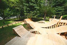 YCAM InterLab+五十嵐淳による北海道札幌の「コロガル公園inネイチャー」です。 「札幌国際芸術祭2014」出展作です。 都心にありながら緑豊かな環境と呼応させるべく北海道産の木材を活用した「公園」とした。先ず丸太を910グリッドで地面に打ち込む。次に丸太の頭をカットする。その柱の頭に、薄いスチールフラットバーを重力のままにそっと置くように設置。自然と湾曲したフラットバーにウッドデッキ材を固定していった。 ※以下の写真はクリックで拡大します               以下、建築家によるテキストです。 ********** 「コロガル公園inネイチャー」 2012年に山口情報芸術センターで発表された「コロガル公園」は、不定型で起伏のある木の空間に、マイクやLED照明など「メディア」を使った仕掛けをもつことで、子どもたちが新しい動きや遊びのルールを生み出すことを触発するインスタレーションでした。今回のSIAF2014では、この「コロガル公園」が初の屋外バージョンとして大通公園の西に位置する札幌市資料館の庭に出現しました。…