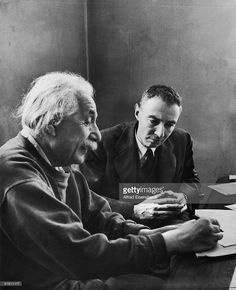 German-born physicist Dr. Albert Einstein (1879 - 1955) (left) writes on a piece of paper as he talk with Dr. Robert Oppenheimer (1904 - 1967) at Princeton's Institute of Advanced Study where both men taught, Princeton, New Jersey, December 1947.