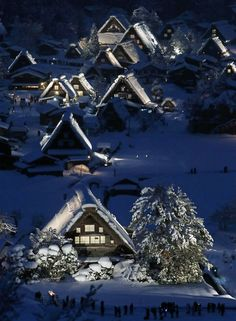 """Japanese traditional wooden houses, """"Gassho zukuri,"""" are lit up in the snow-covered village of Shirakawa in Gifu prefecture, Japan"""
