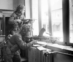 Two British soldiers in position, armed with a Bren and a Sten gun, in a building in Vaucelles, July 1944.
