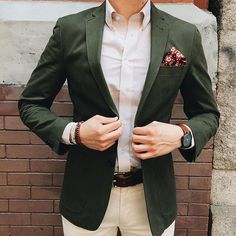 Hunter green jacket with a white button down shirt, printed pocket square, beaded bracelets, and classic leather belt for added detail.