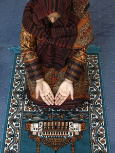 MUSLIM WOMAN KNEELING ON PRAYER MAT SAYING PRAYERS, JORDAN, MIDDLE EAST