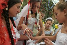 """14 year old roma (gypsy) bride Garoafa Mihai (centre), assisted by friends, organises the """"wedding favours"""" to be given as presents, in Sintesti, Romania, on Sunday, Sept. 24th 2006. Day two of the wedding between Garoafa Mihai, aged 14, and Florin 'Ciprian' Lulu, aged 13, Roma (gypsies) from the village of Sintesti,15 kilometres from Bucharest, Romania. Their partnership was decided by their parents and not through love, and under Romanian law is illegal. The children will neither complete…"""
