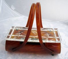 Brown Marbled Lucite Purse by Rialto  Rialto of Brooklyn, New York, was one of the prominent Lucite purse designers in the 1950s. Lucite purses by Rialto were considered quite expensive at the time and sold in fine retail establishments. This stunning purse has a clear carved top and semi-translucent light brown marbleized body with delicately curved handles.
