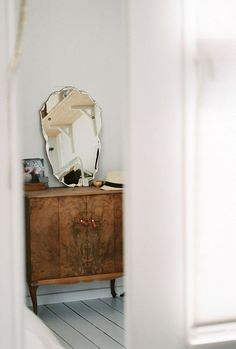 vintage mirror and wood cabinet in entryway