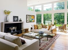 """Handman created two distinct seating areas in the living room: one in front of the fireplace and another, with three comfortable chairs, positioned to take advantage of the view. """"It says, 'Sit down and relax,'"""" he notes."""