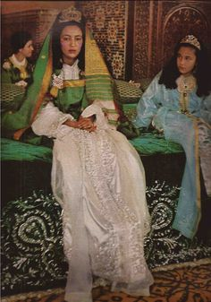 The Kingdom of Morocco spent seven days and seven nights celebrating the joyful occasion of The royal wedding of H.R.H. Princess Lalla Nouzha, sister of the King of Morocco, and Mr. Ahmed ben Mohammed Osman.  Seated beside her younger sister, H.R.H. Princess Lalla Amina, the bride wears  a white satin marriage caftan embroidered in silver and pearls, with a long green and gold veil by a gold diadem. Her ring, paved with diamonds reaches almost to the knuckle.