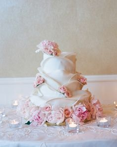 A three-tier cake covered with ruffles and accented by blush roses and peonies.