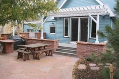 Rose sandstone patio with walls and kitchen/dining area. By Native Edge Landscapes in Boulder, Colorado.