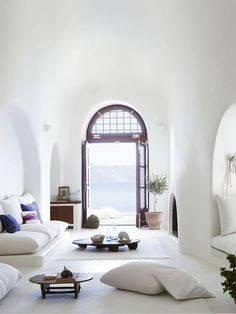 white walls, arched doorways, transom window, cushions