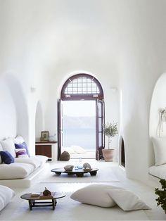 white walls, arched doorways, transom window, cushions