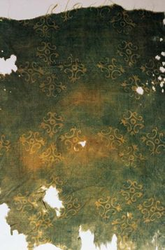 Tang Dynasty. Four-petalled floral design. Small floral patterns were very popular during the Sui to early Tang dynasty. This item has a four-petalled floral design in a lozenge shape. A method of ash-resist dyeing was used here: The resist substance is applied by printing with a small relief block, so that the design areas are sealed off from the dye. After dyeing the fabric green, the resist substance is removed to reveal white designs. China National Silk Museum.