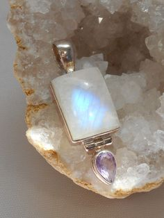 "Highly polished handmade Sri Lankan Rainbow Moonstone gemstone pendant with faceted Amethyst gemstone on a hinged dangle, set in 925-hallmarked sterling silver. Length: 1.5"" including bail. Width: .5"""