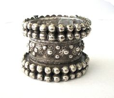 This is a very beautiful high grade silver hinged cuff bracelet from Swat Valley, Pakistan and worn by Pashtun women. The style of bracelet is also worn in Afghanistan. The bracelet dates by other similar example I have seen from the late 19th to early 20th century.  It has a lovely soft silver patina that high silver content jewellery achieves after decades of wear. It has two rows of silverwork shot bands around the top and bottom and decorated in the middle with applied floral and shot…
