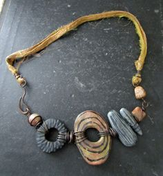 This necklace is made in my classic collage style- bringing together many elements to create one overall piece of one of a kind jewelry. The entire piece is handmade- the focal donut is polymer clay along with the other focal beads as well. Picture jasper and ocean jasper beads are also featured.. The ribbon is recycled sari silk. Wire is all solid copper. This necklace measure about 18. Both sides are shown    please note, due to the nature and shape of this piece, it hangs more like a 16…