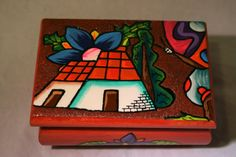 This handmade and hand painted wooden jewelry box is expertly made from reclaimed wood. It is beautifully decorated with vibrant flowers, a butterfly and a rustic house. The box itself is painted a reddish-brown inside and out. The lid is hinged at the back. On the bottom is handwritten, Roatan, Honduras. It would look fabulous on a vanity!  Size: 4.75x3.25x2.25