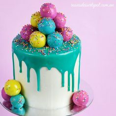 Dripping ganache cake decorated with cake pops. For the video tutorial, visit http://www.youtube.com/c/rosiesdessertspotaustralia