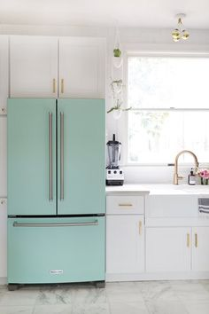White cabinets with a colored fridge accent