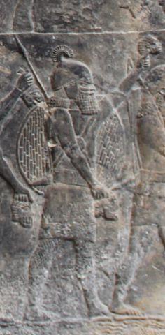 Em detalhe ao relevo, guerreiro assírio erguendo as cabeças de inimigos derrotados