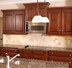 Cherry kitchen cabinets with cook top and island.  Kitchen Ideas