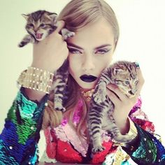 Cara Delavigne with blacked-out lips and a couple kitties.
