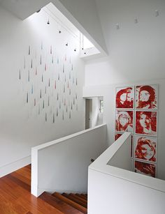 Stairwells are the perfect place to display artwork; this Hamptons home features a series of Vik Muniz works that resemble Andy Warhol's iconic portraits of Jacqueline Kennedy Onassis, but are made with ketchup. Photo by Richard Powers. This originally appeared in Art-Filled Hamptons Vacation Home.