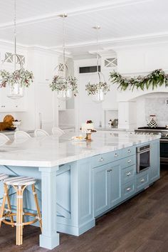 Kitchen with white cabinets and light blue island