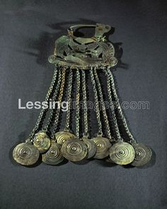 Lessing, Erich, photographer. Large bronze fibula, probably worn as a pectoral, from the necropolis in Hallstatt, Austria. Twelve solar disks on small chains (two missing), hanging from a boat-like brooch with a pair of horses and two birds. Height 30 cm