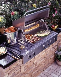 This outdoor kitchen in miniature centers on a grill and cooktop built into a stone wall. Backed into foliage, it's a discreet and useful addition.