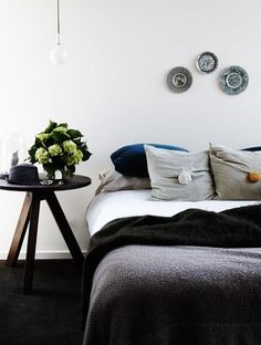 Lovely ideas in this space including plates on the wall and black mohair blanket